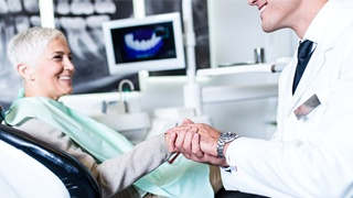 An older woman shaking hands with her dentist