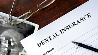 Dental insurance form on desk with pen and glasses