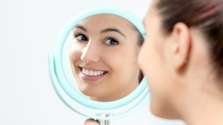 A young woman looking at her new and improved smile in a handheld mirror