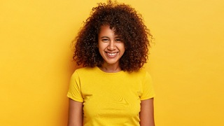 A young woman wearing a yellow t-shirt and smiling with a small gap between her upper two front teeth