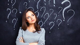 woman in front of chalkboard covered in question marks