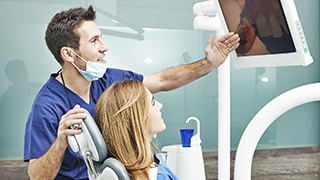 Dentist and patient looking at images on computer