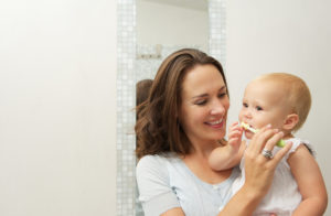 Mother brushing child's teeth