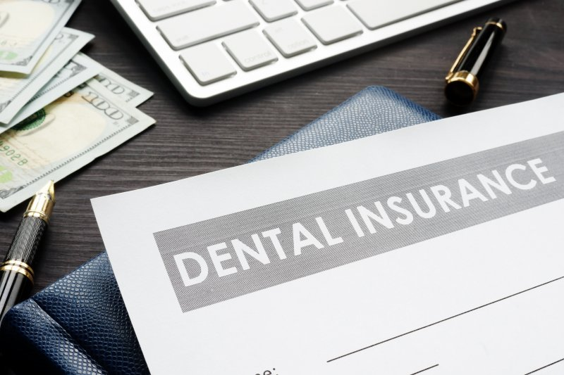 Dental insurance form on desk with money and pens