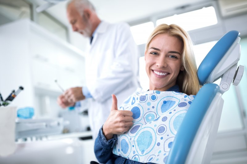 Patient giving thumbs up at routine dental appointment
