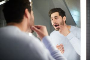 man looking at his loose tooth in the mirror
