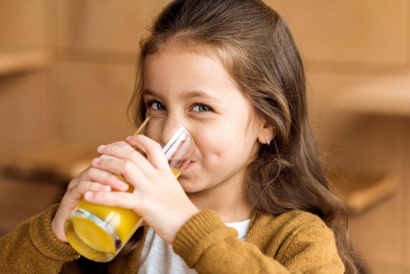 Closeup of young girl drinking orange juice